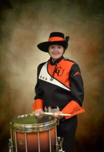Senior Snare Drum Player Kaitlyn Sellers holding a drum in her marching band uniform