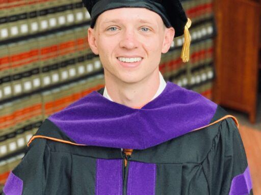 Photo of Hunter Koehl standing in graduation regalia in front of books in the library