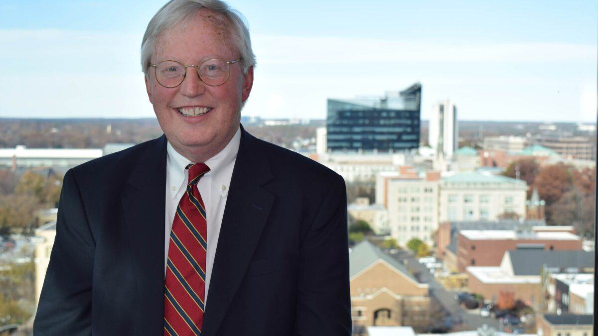 Photo of Judge Robert Rader with downtown Raleigh in background