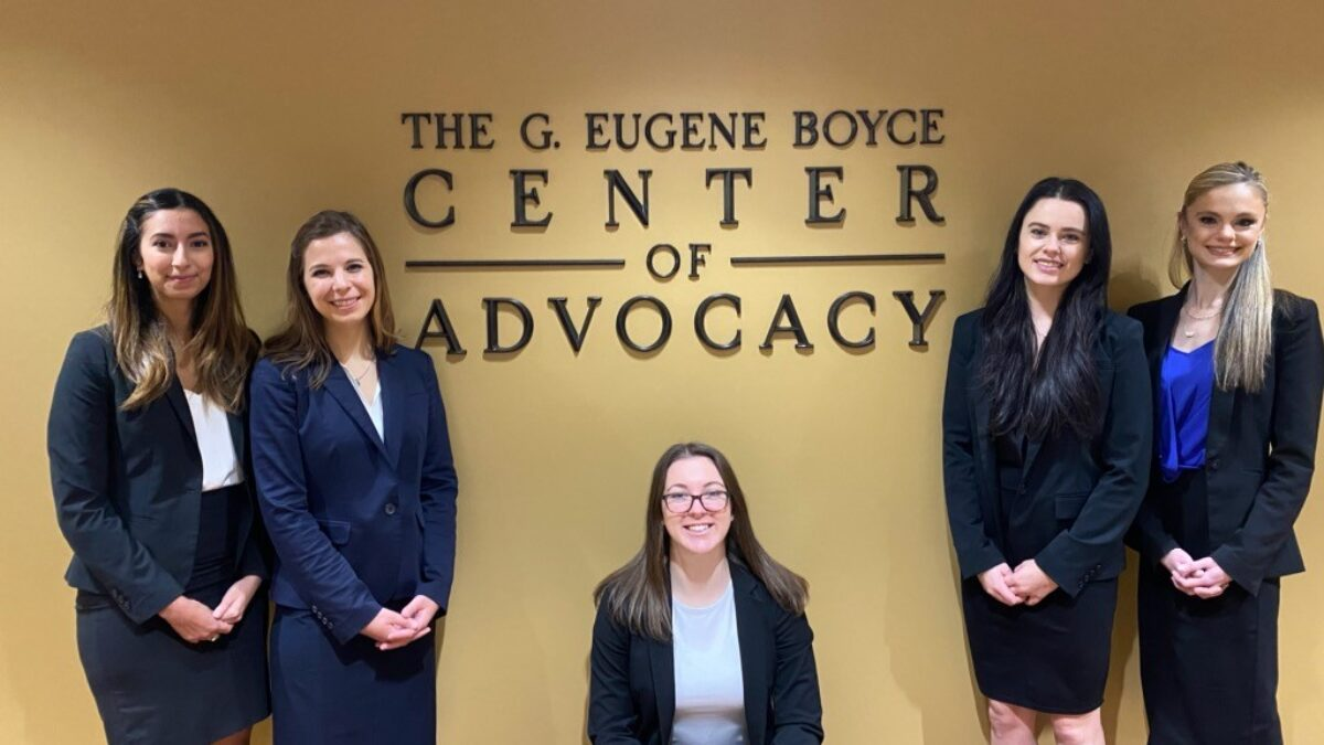 Photo of Savannah Singletary and Oumayma El Hamzaoui, and second-year law students Sierra Lindquist, Kara Goray, and Rebeka Parent,posing in front of the Gene Boyce Advocacy Center sign