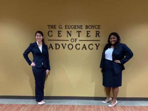 Photo of Veterans Competition advocates posing in front of the Gene Boyce Advocacy Clinic sign.