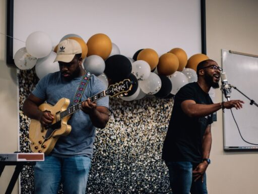 Photo of Brandon Irabor '21 playing guitar and Dean Evin Grant singing in to a mic