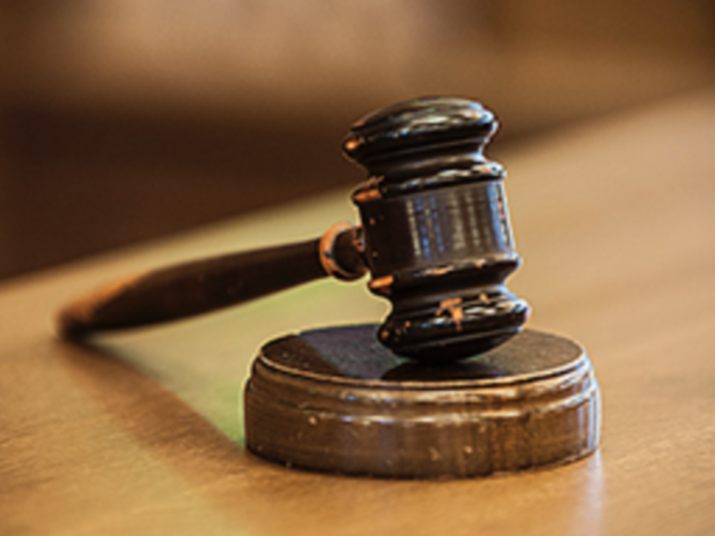 Photo of a wooden gavel on a courtroom bench