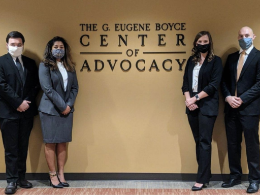 Photo of King of the Hill Trial Competition Advocates posing with masks on in front of Gene Boyce Advocacy Center sign.