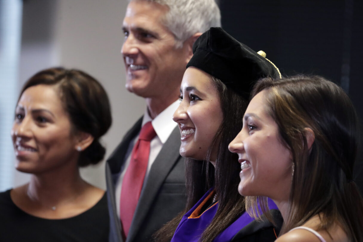 Photo of graduate with her family at hooding ceremony at Campbell Law School, August 9, 2020.