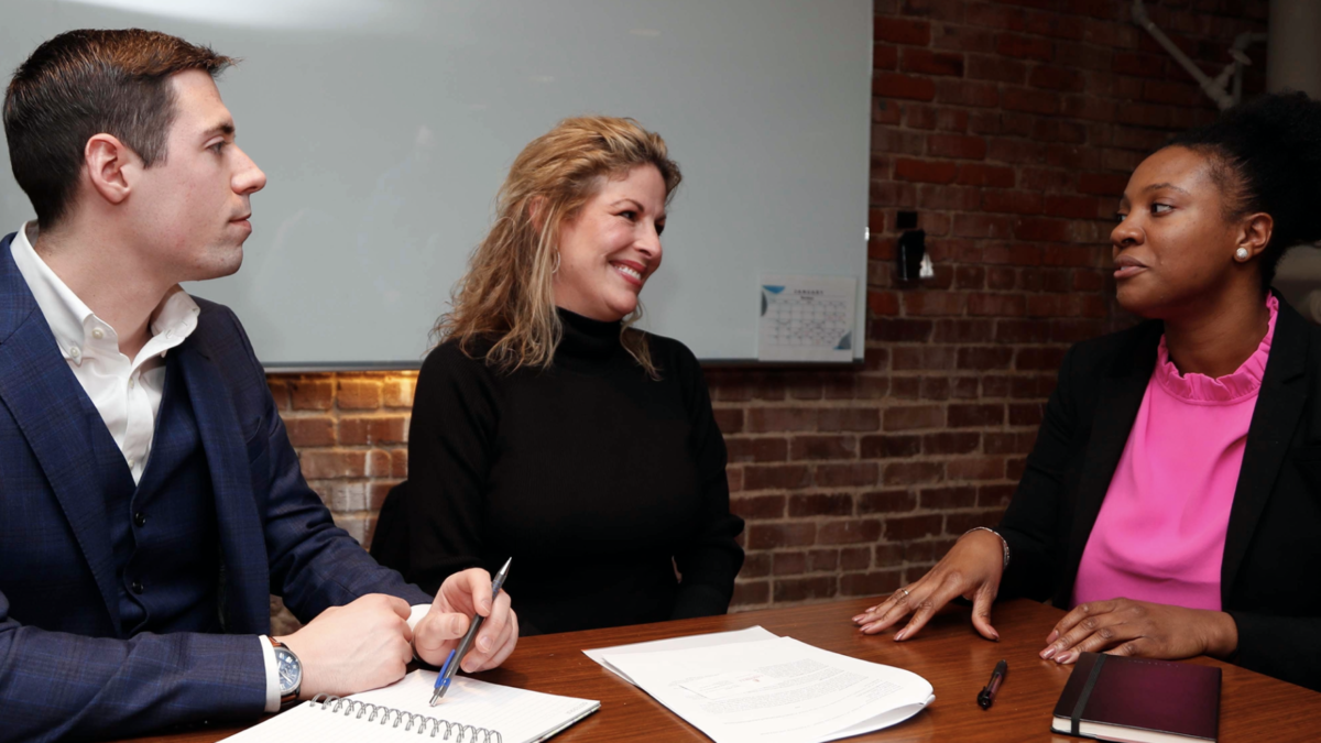Photo of two Business Law Clinic students sitting at a table with a female client